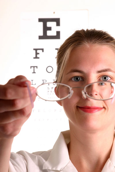 optician holding eyeglasses, with a blurred vision chart