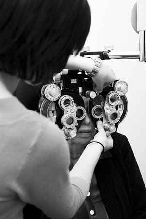 woman looking through a phoropter as an optician tests her eyesight